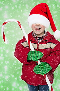 boy in red jacket, red Santa hat and green gloves holding large candy cane
