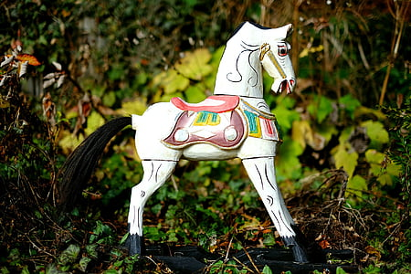 white wooden horse on ground macro photo