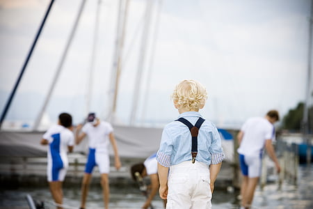 blonde boy wearing blue shirt standing near body of water
