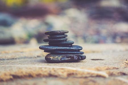 stack of black rocks on gray concrete pavement