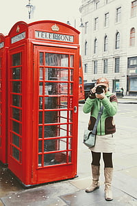 woman holding camera standing near telephone booth