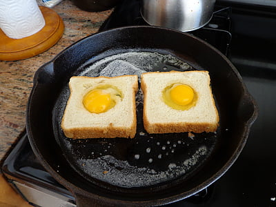two slice bread with eggs on skillet