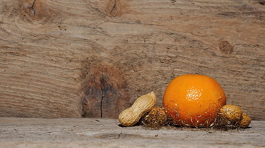 orange and peanuts on brown wooden board