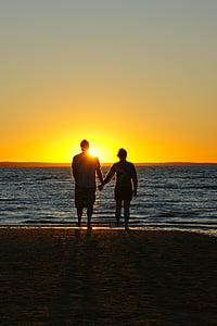 couple holding hands near beach during golden hour