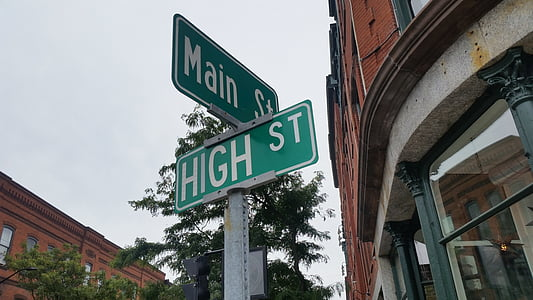 Main st. and High st. street sign under gray sky at daytime