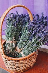 purple flowers in brown wicker basket