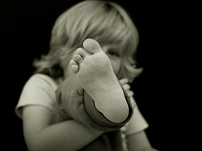grayscale photography of children showing foot