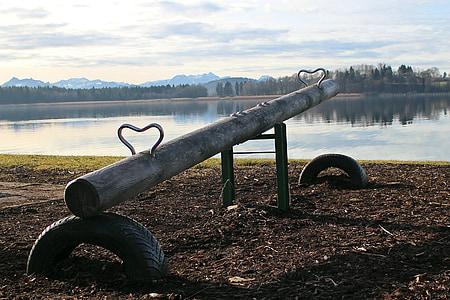 brown wooden log seesaw near water
