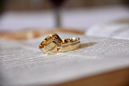 gold-colored wedding bands on bible