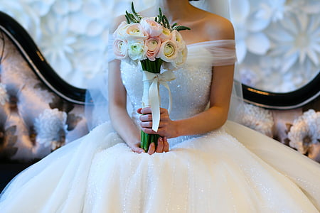 bride holding white and pink bouquet of flowers