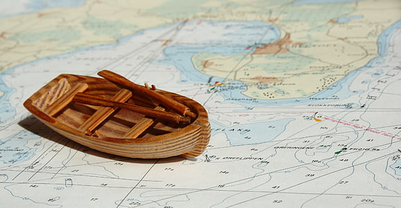 brown wooden miniature boat on top of map