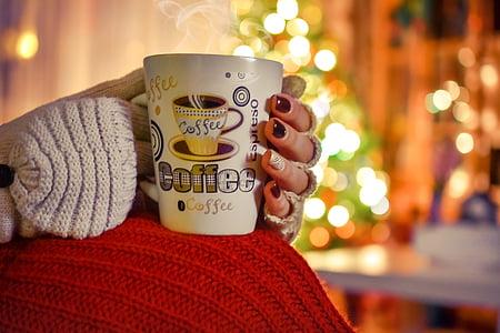 woman holding white ceramic coffee mug