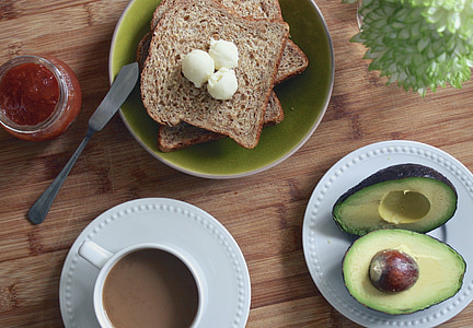 photo of avocado on plate beside sliced breads