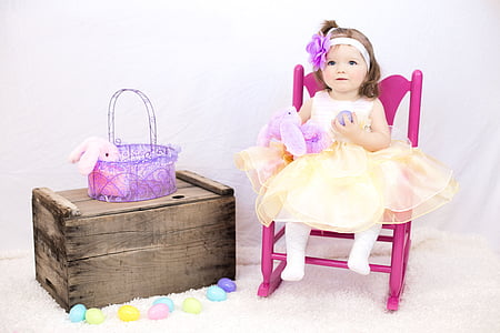 girl doll sitting on pink rocking armchair beside the brown wooden box
