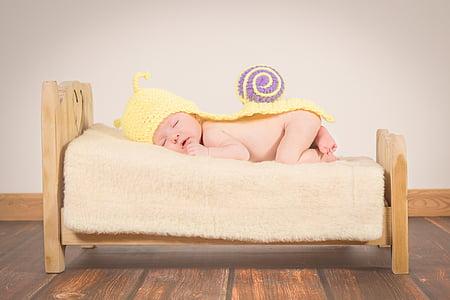 baby wearing yellow hat lying on sofa