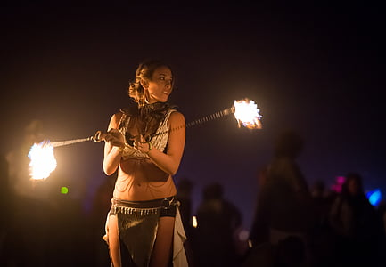 a woman fire dancing in night time
