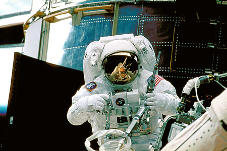 astronaut holding equipment