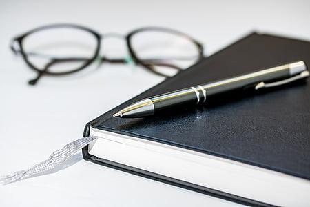black pen on top of black book