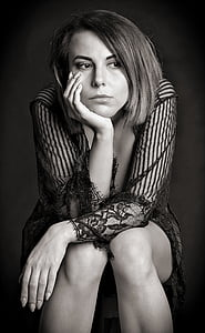 woman sitting on black background