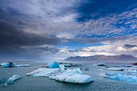 iceberg near mountain at daytime