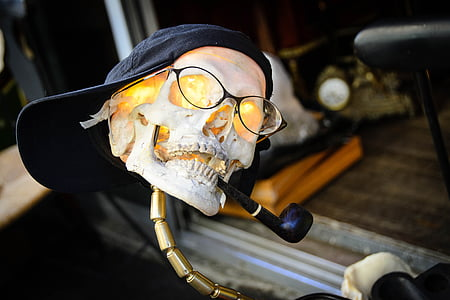 human skull decor with eyeglasses, cap, and tobacco pipe