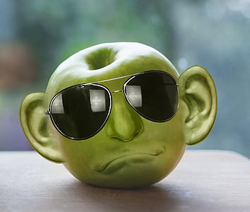 green apple formed into face with sunglasses