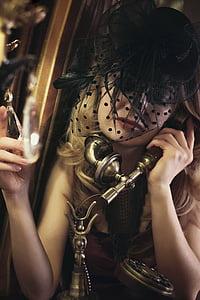 woman in black fascinator hat holding gold crank phone