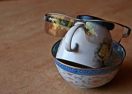 close photo of sunglasses on white ceramic tea cup