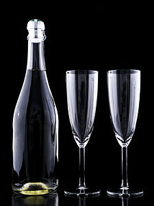 two clear flute champagne glasses and bottle