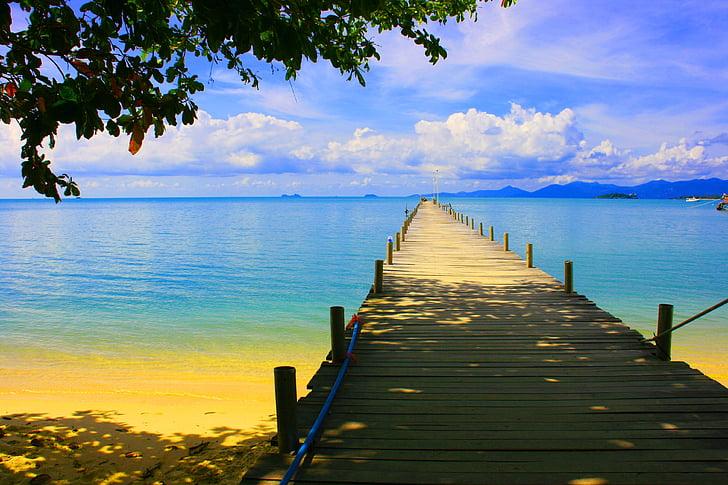 tan wooden sea dock across calm sea during daytime