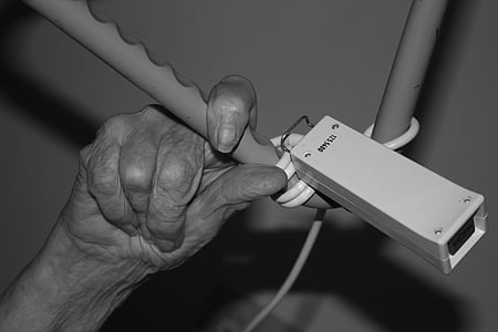 persons hand on gray metal bar