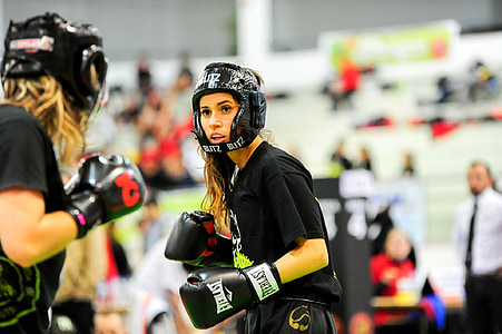 two woman wearing boxing sparing helmet and gloves