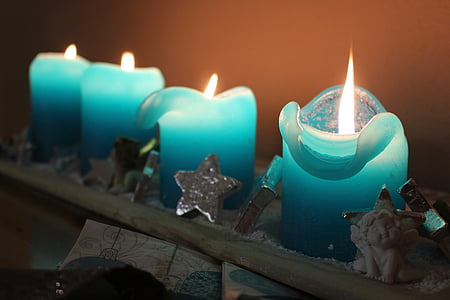 time lapse photography of four blue lighted candles