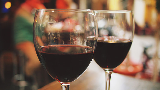 clear wine glasses filled with red wines