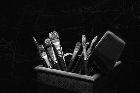 greyscale photo of paint brushes in box