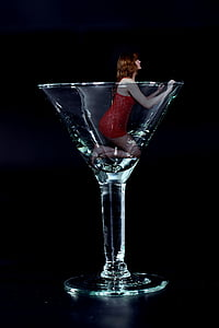 woman wearing red sleeveless dress in clear cocktail glass