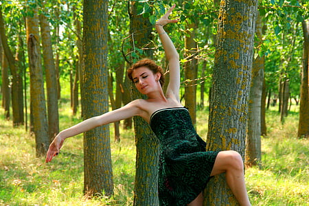 woman wearing black strapless dress making a pose in a forest