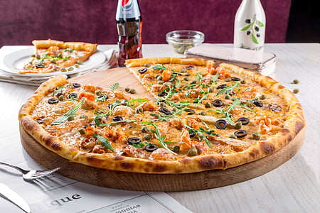baked olive pizza on table