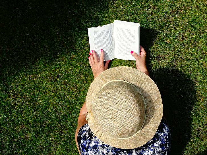 woman wearing beige hat reading book