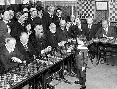 grayscale photo of group of men vs boy playing chess game