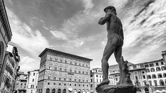 grayscale photo of Statue of David near buildings