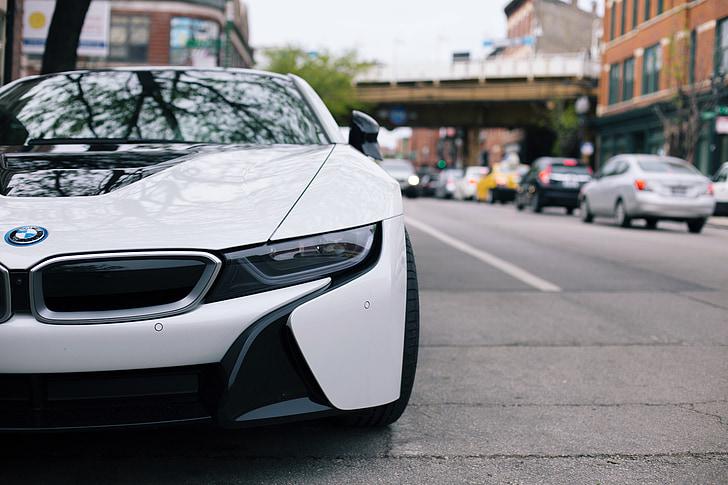white BMW car parking on road
