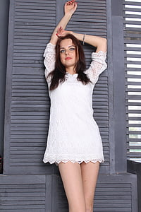 woman wearing white lace short-sleeved mini dress leaning on black wooden wall