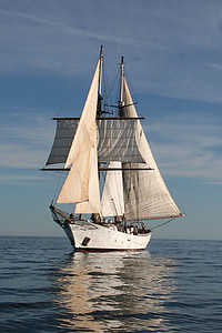 photo of white sail ship in body of water