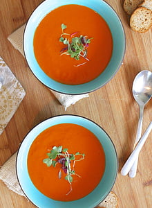 two orange soups on teal ceramic bowls