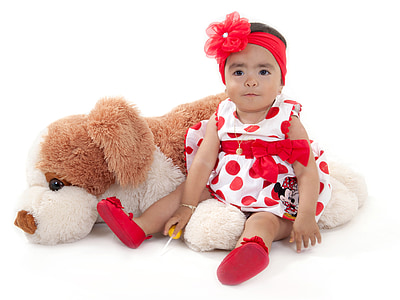 baby wearing white and red polka-dot dress beside dog plush toy