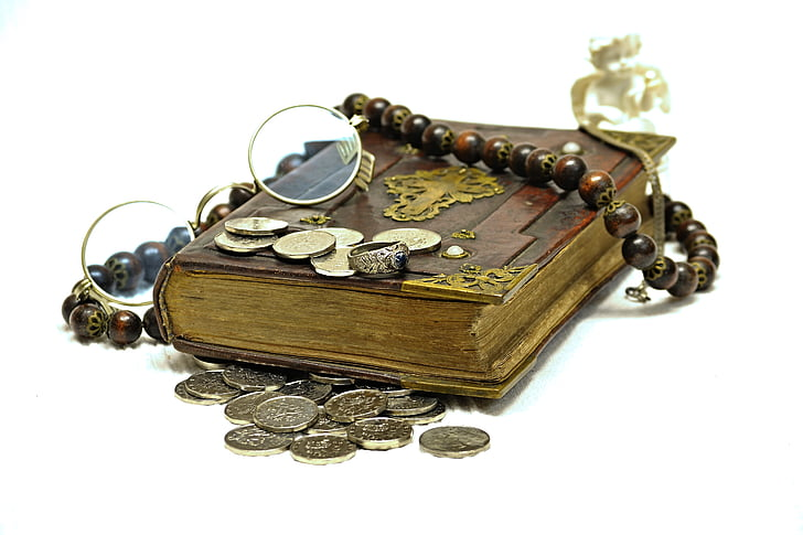 brown book and coins on white surface