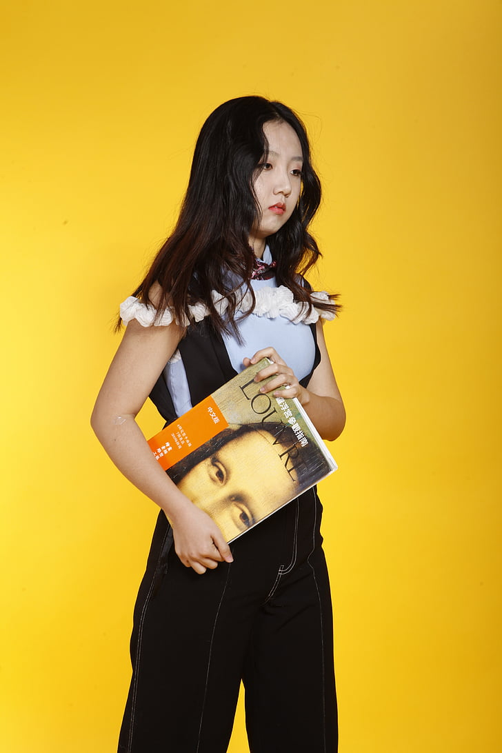 girl holding book facing sideways