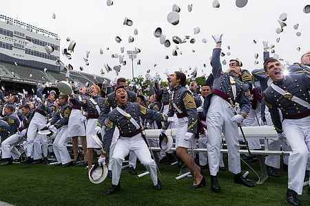 new graduates throwing their hats on the air during daytime