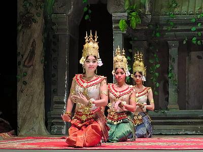 three kneeling women wearing traditional dresses